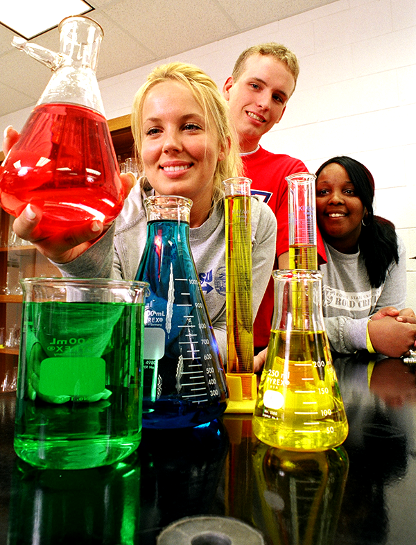 Students looking at beakers filled with colored liquids.