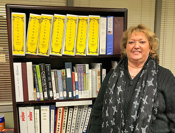 Director Shellie McGill standing next to RSU Library's growing Textbook and Required Reading Reserve Collection housed at Bartlesville Public Library