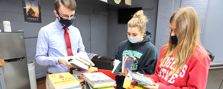 Students looking through a stack of books.