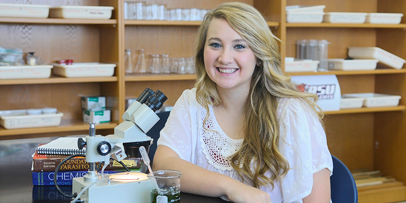 Girl in lab next to microscope