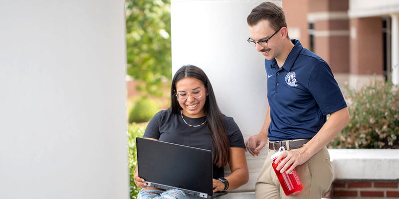 Professor and Student looking at Laptop Outside